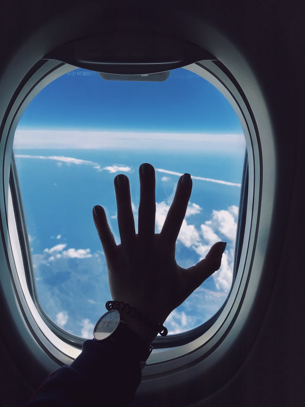 photography of person s left hand touching an airplane s window